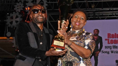 The Minister of Culture, Gender, Entertainment and Sport, the Honourable Olivia Grange presents trophy to Jamaica Festival Song Winner 2019, Raldene 'Loaded Eagle' Dyer