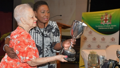 The Minister of Culture Gender, Entertainment and Sport, the Honourable Olivia Grange (right) accepts donations for the National Sport Museum from former hockey player and administrator, Kay Wilson.
