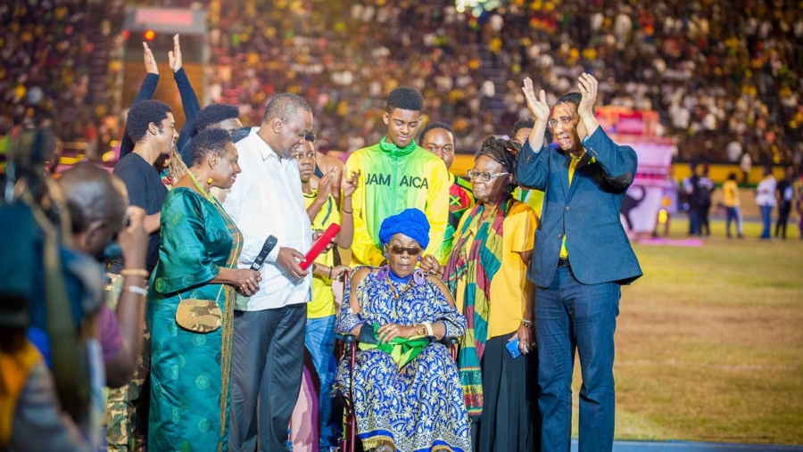 Prime Minister, the Most Hon. Andrew Holness (right) applauds Rita Marley (seated) after she was presented with the Jamaican Reggae Icon Award on Independence Day at the Grand Gala at the National Stadium.  Also sharing the moment are the President of Kenya, His Excellency Uhuru Kenyatta; the Minister of Culture, Gender, Entertainment and Sport, the Honourable Olivia Grange; and members of the Marley family.