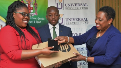 The Honourable Olivia Grange, Minister of Culture, Gender, Entertainment and Sport (right) accepts the donation of laptops and tablets from Deleen Powell, marketing Manager, Universal Service Fund while the Minister of State in the Ministry of Foreign Affairs and Foreign trade and Chairman of the Youth Advisory Committee of the Jamaica National Commission for UNESCO, the Senator the Honourable Pearnel Charles Jr looks on.