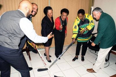 Poke checking. The Honourable Olivia Grange, Minister of Culture, Gender, Entertainment and Sport prepares to poke the puck away from Greame Townsend, National Hockey Coach (2nd left) as it is being released by Donovan Tait, hockey player and coach (left). Looking on in anticipation are: Dorothy McLeod, Director, California Cultural Alliance (3rd left); founding members of the Jamaica Olympic Ice Hockey Federation Judith Smith (4th left) and Lester Griffin (right). The Jamaica Olympic Ice Hockey Federation and representatives from Tropical Ice Ventures of Canada paid a Courtesy Call on the Minister today (December 1) at her offices in Kingston.