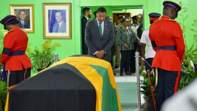 The Most Honourable Andrew Holness and behind him is the  Minister of Culture, Gender, Entertainment and Sport, The Honourable Olivia Grange paying their respects at the Jamaica Labour Party head office.