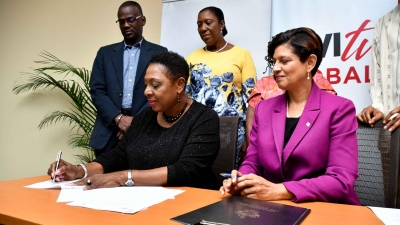 The Ministry of Culture, Gender, Entertainment and Sport, the Honourable Olivia Grange (left) signs the Memorandum of Understanding with the UWI Open Campus for sexual harassment training in workplaces.  The Pro-Vice Chancellor and Principal of the UWI Open Campus, Dr Luz Longsworth (seated right) as well as the Permanent Secretary in the Ministry, Denzil Thorpe (standing left) and the Senior Director of the Bureau of Gender Affairs, Sharon Robinson (standing 2nd left) look on.