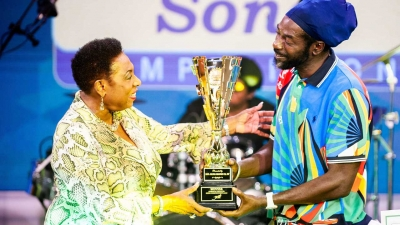 The Minister of Culture, Gender, Entertainment and Sport, the Honourable Olivia Grange (left) presents the Jamaica Festival Song trophy to Buju Banton. The Reggae singer was named winner of the competition on Sunday (July 26) following a public vote.