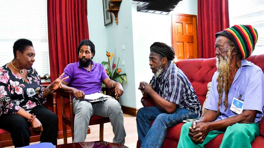 The Minister of Culture, Gender, Entertainment and Sport, the Honourable Olivia Grange (left) in discussion with Coral Gardens Incident Survivor, Ras Walter Brissett (right) and members of Rastafari Coral Gardens Benevolent Society (l-r) Ras Gregory Taylor, Chairman; and Ras Samuel Brown, Treasurer in Montego Bay, St James in July 2019.