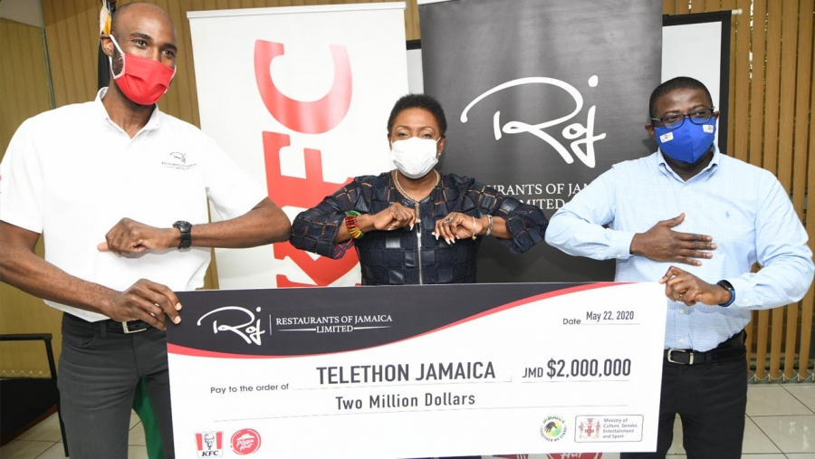 The Minister of Culture, Gender, Entertainment and Sport, the Honourable Olivia Grange (centre) does elbow bumps with with the Brand Manager of the Restaurants of Jamaica Group, Andrei Roper (left) and the Chief Executive Officer of the National Health Fund, Everton Anderson on Friday at her offices in New Kingston.  Restaurants of Jamaica presented a symbolic cheque of J$2M to Telethon Jamaica to provide PPE for frontline workers.  The NHF is the government agency procuring the PPE.