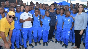 Minister of Culture, Gender, Entertainment and Sport, the Honourable Olivia Grange and the Minister of Labour and Social Security and Member of Parliament for North East St Ann, the Honourable Shahine Robinson (right) with Peter Gould, owner of Mount Pleasant Academy (left) and students at the Drax Hall Sports Complex in St Ann.