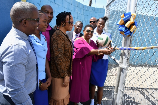 The Honourable Olivia Grange, Minister of Culture, Gender, Entertainment and Sport cuts the ribbon to signal the official opening of the netball court at the Gaynstead High School. Looking on are: Fabian Brown, Caretaker, Trafalgar Division; Kelsey Jonas, netballer; Pastor Derrick Brown, Board Member, Gaynstead High School, Dr. J. Boyd-Vassell, Principal, Liston Aiken, Vice Principal; Major Clifton Lumsden, Chairman, School Board and Latonya Williams, netballer.
