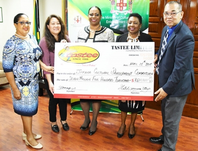 The Honourable Olivia Grange, Minister of Culture, Gender, Entertainment and Sport poses with the replica sponsorship cheque for the Jamaica Independence Festival Song Competition 2018 with Mrs. Patsy Latchman-Atterbury, CEO of Tastee Limited at the Ministry on Thursday, April 26. Joining in from left are Ms. Pat Reid, a member of the Festival Song organizing committee, Ms. Simone Changpong, Director of Tastee Limited and Mr Orville Hill, Interim Executive Director at the JCDC.