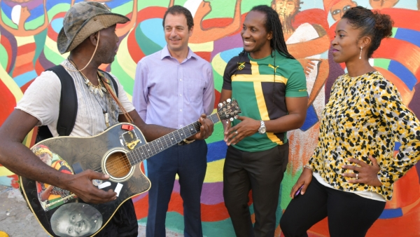 Minister of State in the Ministry of Culture, Gender, Entertainment and Sport, Hon. Alando Terrelonge (second right); and (from second left) Chief Executive Officer, PaperBoyJA, Geoff Lewis; and Co-Founder, Kingston Creative, Andrea Dempster-Chung, are entertained by artiste, Michael Enkrumah, following the launch of Kingston Creative's 'First 50 Impact Investment Campaign' at F&B Downtown, 107 Harbour Street in downtown Kingston on Tuesday (November 27).