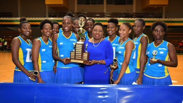 Minister of  Culture, Gender, Entertainment and Sport, the Honourable Olivia Grange, holds the trophy with her alma mater, Gaynstead High School the new senior and junior ISSA Urban Area Netball champions