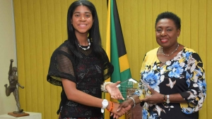 Minister of Culture, Gender, Entertainment and Sport, the Honourable Olivia Grange, receives the DUSUSU Award in the Gender Minister category from the world renowned girls education advocate Zuriel Oduwole.  Minister Grange was honoured for her exemplary work in girls education, gender development and teenage pregnancy.
