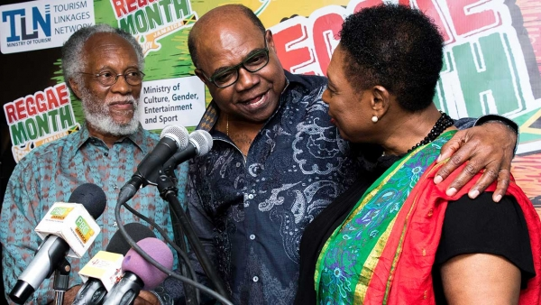 The Minister of Culture, Gender, Entertainment and Sport, the Honourable Olivia Grange (right) embraces the Minister of Tourism, the Honourable Edmund Bartlett, after he announces financial support towards the further development of the Jamaica Music Museum.  Looking on is Director/Curator of the museum, Mr Herbie Miller.