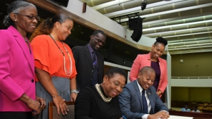 The Minister of Culture, Gender, Entertainment and Sport, the Honourable Olivia Grange (seated left) and the Minister of State in the Ministry of Education, Youth and Information, the Honourable Floyd Green sign a Letter of Commitment towards the implementation of 'The Policy for the Reintegration of School-Age Mothers into the Formal School System'. The signing took place at a Stakeholders' Forum organised by the Women's Centre of Jamaica Foundation at the Jamaica Conference Centre on Thursday. Looking on are: Dr Zoe Simpson, Executive Director, Women's Centre of Jamaica Foundation; Debby-Ann Brown-Salmon, Chairman, WCJF; Denzil Thorpe; Permanent Secretary in the Ministry of Culture, Gender, Entertainment and Sport and Dasmine Kennedy, Deputy Chief Education Officer (Acting) Schools Operations, Ministry of Education, Youth and Information (left to right).