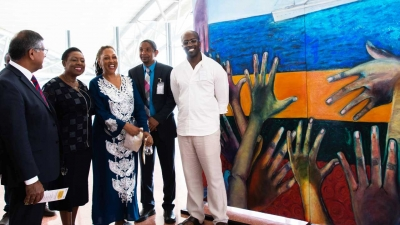 The Minister of Culture, Gender, Entertainment and Sport, the Honourable Olivia Grange (second left) shares a light moment with artist, Rosemarie Chung (centre) at the Unveiling of the Windrush Mural Exhibition at the Norman Manley International Airport on Thursday, 29 August 2019. Sharing the moment are: the British High Commissioner, His Excellency Asif Ahmad (left); The Mayor of Kingston, His Worship Senator Councillor Delroy Williams (second right); and Chief Curator at the National Gallery of Jamaica, O'Neil Lawrence (right).