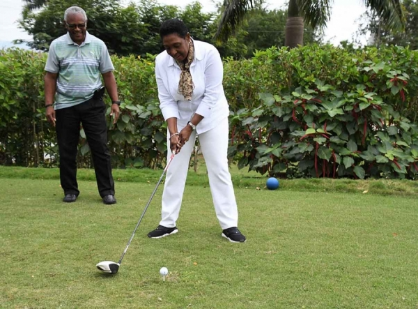 The Honourable Olivia Grange, Minister of Culture, Gender, Entertainment and Sport is all set to tee off. Looking on is Major Desmon Brown, Organiser of the Jamaica Professional Golf League Series.