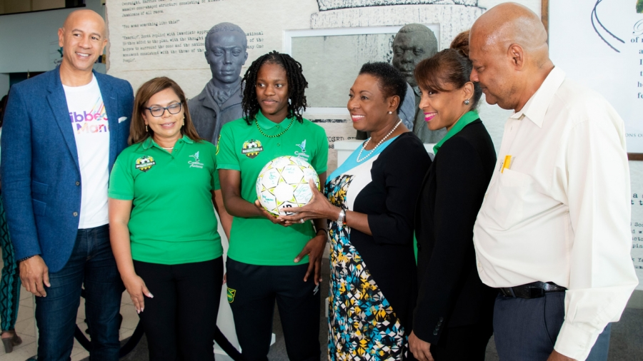 Minister of Culture, Gender, Entertainment and Sport, the Honourable Olivia Grange (3rd right), receives from Reggae Girlz captain Konya Plummer a football signed by members of the team.  The Reggae Girlz departed Jamaica on Monday to begin final preparation for the FIFA Women's World Cup in France.  Sharing the moment are JFF President, Michael Ricketts (r) and from Caribbean Airlines: Zachary Harding, Director; Alicia Cabrera, Senior Marketing Manager; and Trudy Chin, General Manager.