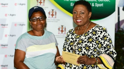 Minister of Culture, Gender, Entertainment and Sport, the Honourable Olivia Grange presents grant to Violet Morris-Peddie at the Ministry's Economic Opportunities Workshop in Accompong, St Elizabeth.  The Minister awarded 50 grants to small businesses to boost the cultural economy in Accompong.