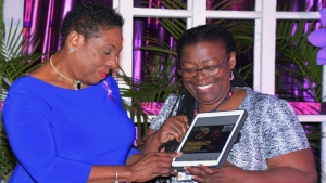 The Minister of Culture, Gender, Entertainment and Sport, the Honourable Olivia Grange signs the online gender-based violence platform. Also photographed is Vilma Gregory, Advocacy and Communications Consultant, UNFPA Caribbean Sub-Region Office (right).