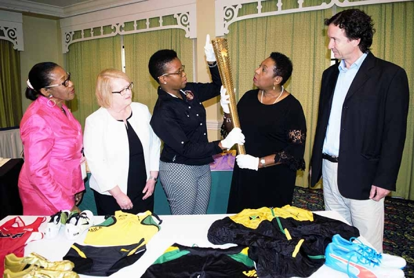 A close look is being taken at a replica of the 2012 London Olympics torch by the Honourable Olivia Grange, Minister of Culture, Gender, Entertainment and Sport (second left); Florette Blackwood, Senior Director, Sport Development and Monitoring Division in the Ministry; Janice Smith, National Sport Museum Consultant; Colleen Nattie, Conservation Officer, National Museum Jamaica and Dr Johnathon Greenland, Curator, National Museum Jamaica (left to right). The torch along with other donated items for the National Sport Museum was on display at the Textile Conservation, Preservation and Exhibition Workshop today (Wednesday) at the Knutsford Court Hotel in Kingston.