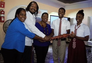 The Honourable Olivia Grange, Minister of Culture, Gender, Entertainment and Sport hands over the Reparations Baton to head boy Daneil Reid and head girl Renae Robinson of Paul Bogle High School (2nd r-l). Also photographed are: Lorraine Williams, teacher, Paul Bogle High School and Steven Golding, Chairperson of the Events/Outreach and Public Education Committee, National Council on Reparations. Tomorrow (October 19) students and young people will run with the Reparations Baton from Paul Bogle High School to the Old Courthouse where the Baton will be handed over to the Mayor after which the Rally will commence.