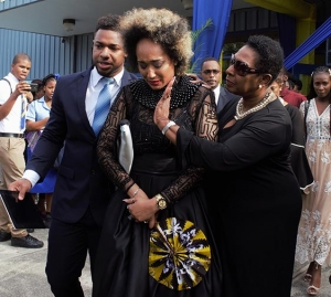 The Honourable Olivia Grange, Minister of Culture, Gender, Entertainment and Sport consoles Kelly-Ann Boyne, daughter of the late Ian Boyne as she and her brother Andre Skeen (left) depart the National Indoor Sports Centre where the Thanksgiving Service for the life of their father was held today (Sunday).