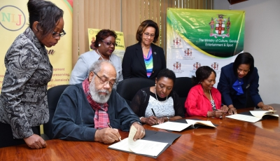 The Honourable Olivia Grange, Minister of Culture, Gender, Entertainment and Sport (centre) signs the Deed of Gift under which the Coverley Collection has been turned over to the National Library of Jamaica, an agency of the Ministry. The document was also signed by Fabian Coverley, son (second left) and Judge Pamela Appelt, Co-Executor, Louise Bennet Coverley Estate (second right), who is being assisted by Deon Ellignton, Team Leader, Advantage General Insurance Company Limited who signed as a witness (right). Looking on are: Georgette Grant, Legal Officer in the Ministry; Beverley Lashley, CEO, National Library of Jamaica and Marigold Harding, Deputy Chair, Institute of Jamaica (left to right).