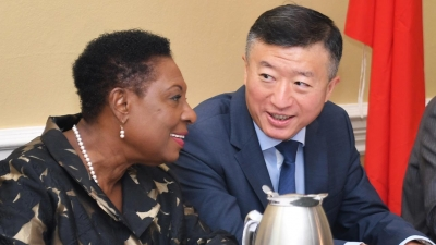 The Minister of Culture, Gender, Entertainment and Sport, the Honourable Olivia Grange (left) shares a light moment with the Ambassador of the People's Republic of China to Jamaica, His Excellency Tian Qi.  They were at the official send-off for the second batch of 138 Jamaican athletes and coaches who will receive specialised training in China under a sports cooperation agreement between both countries.