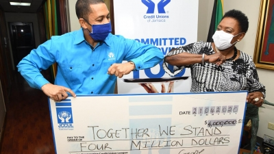 The Minister of Culture, Gender, Entertainment and Sport, the Honourable Olivia Grange (right) does an elbow bump with the Group Chief Executive Officer of the Jamaica Co-operative Credit Union League, Mr Robin Levy as he presents her with a symbolic cheque of the JCCUL's J$4M contribution to Telethon Jamaica: Together We Stand. The six hour, virtual telethon raised funds to provide Jamaica's frontline workers with equipment to battle Covid-19.