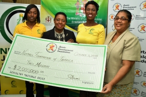 The Honourable Olivia Grange, Minister of Culture, Gender, Entertainment and Sport (2nd left) presents President, Netball Jamaica, Paula Daley-Morris (2nd right) with a cheque valued at J$2M towards the staging of the upcoming Sunshine Series. Also photographed are: Sunshine Girl, Shanice Beckford and Charmaine Hanson, Financial Controller, Sports Development Foundation (l-r).