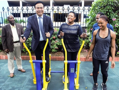 Getting Fit. Minister of Culture, Gender, Entertainment and Sport, the Honourable Olivia Grange and Li Sen, President, Board of Supervision, China Communications Construction Company try out newly installed equipment at Emancipation Park earlier today (Wednesday). The gym equipment was donated by China Harbour Engineering Company. The donation supports the Ministry's goal for a more active and healthier society as outlined in the National Sport Policy. Looking on are: Fitness Instructor Davina Barrett (right); Member of Parliament East Central St. Catherine, Alando Terrelonge (partially hidden) and Doran Dixon, Director, National Housing Trust (left).