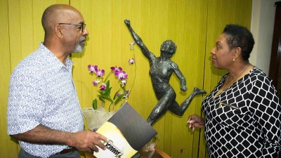 The Minister of Culture, Gender, Entertainment and Sport, the Honourable Olivia Grange (right) discusses the design of the Shelly-Ann Fraser Pryce statue with sculptor Basil Watson.