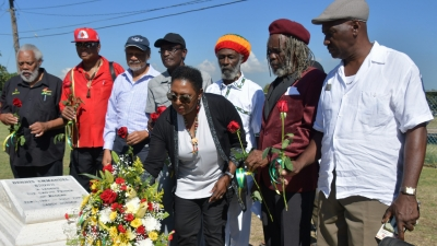 Minister of Culture, Gender, Entertainment and Sport, the Honourable Olivia Grange makes a Floral Tribute at the resting place of Dennis Brown (National Heroes Park) on the anniversary of his 62nd birthday and as part of activities to celebrate Reggae Month. Also photographed are: Ibo Cooper, Chairman, Jamaica Reggae Industry Association; Copeland Forbes, producer/manager; Junior Lincoln, producer/manager; Lloyd Parks, band leader/reggae vocalist; Sangie Davis, musician; Trevor 'Leggo' Douglas, owner of Leggo Records and Paul 'Jah Screw' Love, producer/musician (left to right).