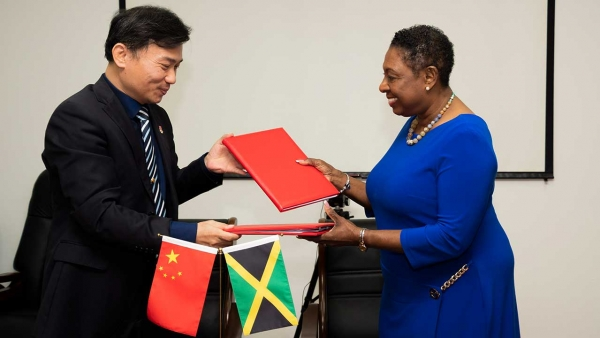 Minister of Culture, Gender, Entertainment and Sport, the Honourable Olivia Grange (right) signs major sport cooperation agreement with the General Manager of the state-owned China Sport International Company, Mr Lu Guoguang (left).  Under the agreement, more than 400 athletes from Jamaica will receive high level training at specialised centres in China over the next three years.
