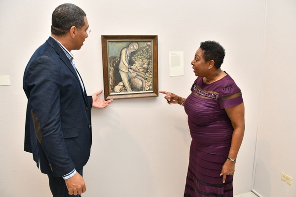 Minister of Culture, Gender, Entertainment and Sport, the Honourable Olivia Grange points out a feature in John Dunkley's piece titled The Shepherd to Prime Minister, the Most Honourable Andrew Holness. The Prime Minister declared open the exhibition John Dunkley: Neither Day nor Night on Sunday at the National Gallery of Jamaica. The Good Shepherd is an allegorical portrait of National Hero, the Right Excellent Sir Alexander Bustamante.