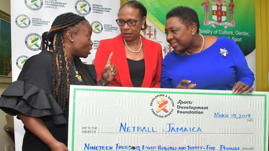 The Minister of Culture, Gender, Entertainment and Sport, the Honourable Olivia Grange (second left) hands over a cheque for 3.5 million dollars to the 1st Vice President of Netball Jamaica, Tricia Robinson (left) to assist with funding the Sunshine Girls for the 2019 World Cup in Liverpool.  Also photographed is Molly Rhone, President, International Netball Fedration.