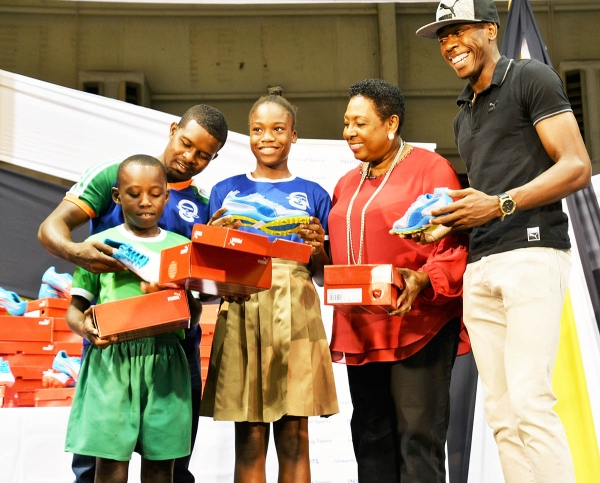 Minister Grange is joined by 400m Olympian Javon Francis in the start of presentation of 400 pairs of spikes to primary schools. First recipients are the coach and students from the Naggo Head Primary School, winners of last year's Primary Schools Champs.