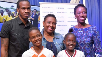 The Minister of Culture, Gender, Entertainment and Sport, the Honourable Olivia Grange (centre); Ian 'Pepe' Goodison, former national football player and ambassador for the INSPORTS Primary School Football Competition and Dr Paula Daley-Morris, President, Netball Jamaica with Anthony McDonald, captain, Denham Town Primary School football team (front, left) and Shawna-Kay Davis, captain Greenwich Primary School netball team.