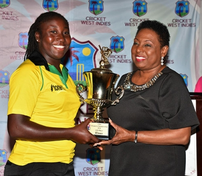 The Honourable Olivia Grange, Minister of Culture, Gender, Entertainment and Sport (right) presents Stafanie Taylor, Jamaica Women's Cricket Team Captain with the winner's trophy for Jamaica coming out on top in the Cricket West Indies Regional T20 Blaze tournament played in Jamaica in June. The award was presented during the Closing Ceremony for the tournament at Hotel Four Seasons on Sunday, June 24.