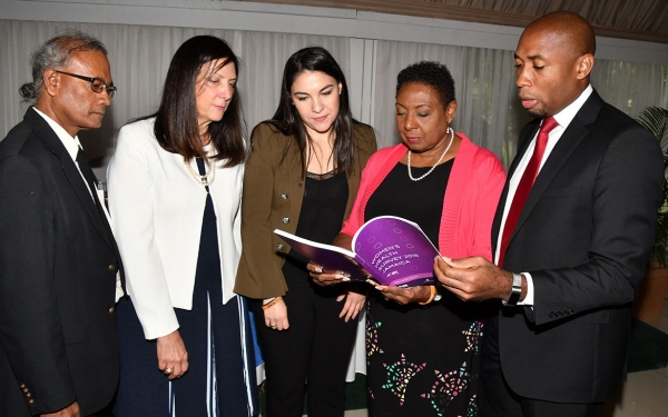 The Honourable Olivia Grange, Minister of Culture, Gender, Entertainment and Sport (second right) reads a section of the Jamaica Women's Health Survey which was launched at the Terra Nova Hotel today, June 21. Also Photographed are: Easton Williams, Senior Director, Social Policy Planning and research Division, Planning Institute of Jamaica and Chair of National Steering Committee; Luiza Carvalho, Regional Director, Americas and the Caribbean, UN Women; Camila Mejia Giraldo, Modernisation of the State Specialist, Inter-American Development Bank and Rohan Richards, Chief Technical Director, Ministry of National Security (left to right).
